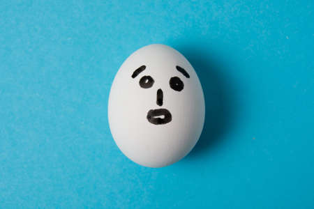 Egg with a surprised face. Isolate on a blue background.