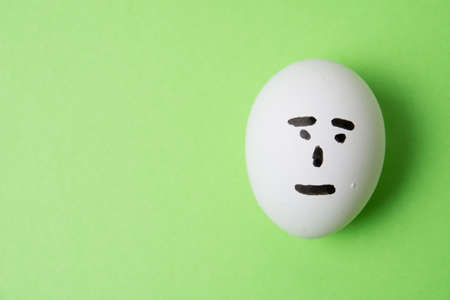 An egg with an indifferent emotion on the face, on a green background copy space.