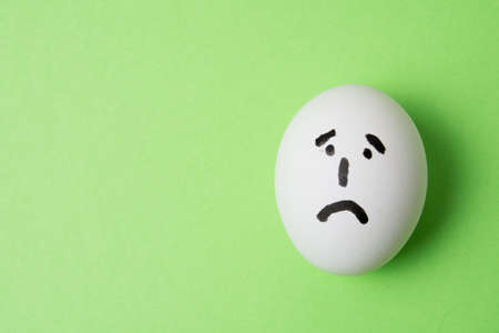 Egg with a very sad emotion on the face, on a green background with copy space Standard-Bild