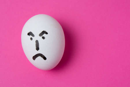 An egg with an evil face, on a pink background with copy space. Standard-Bild