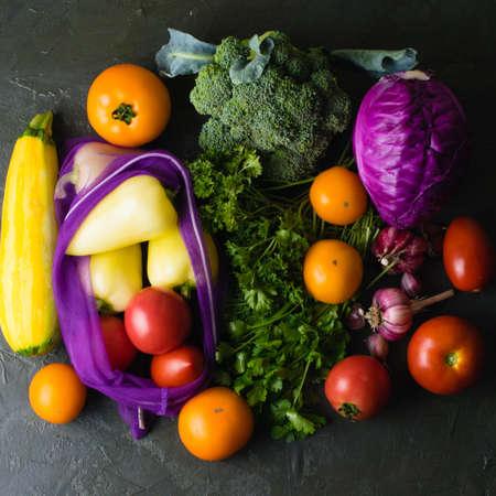 Lots of vegetables: garlic, cabbage, broccoli, cilantro, parsley and tomatoes on a dark tabletop. Vegetables in a reusable fruit and vegetable bag. Ecology protection concept. Archivio Fotografico