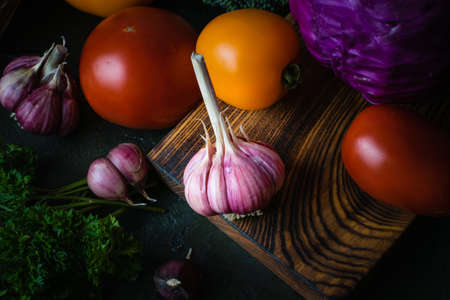 Vegetables on a cutting board on a dark table top. Vegan food and cooking concept