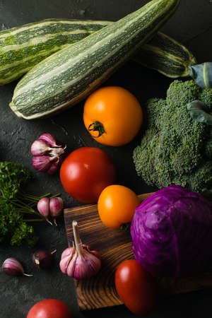 Healthy nutrition concept. Lots of vegetables on a dark table top, view from the top. Archivio Fotografico