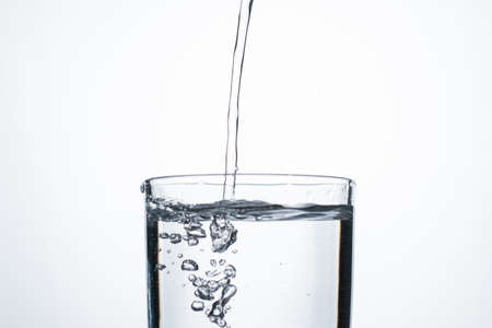 Jet of water or alcohol is pouring into a glass with splashes and bubbles, copy space.