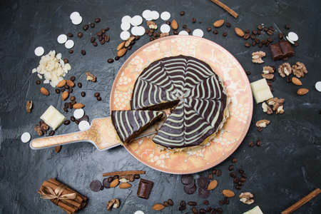 Chocolate sliced esterhazy cake with cream, frosting, nuts, cinnamon and almonds close-up view from the top on an orange-brown plate, on a dark concrete background. Archivio Fotografico