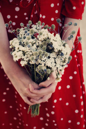 Bouquet of wild flowers in female hands close up woman in vintage red dress