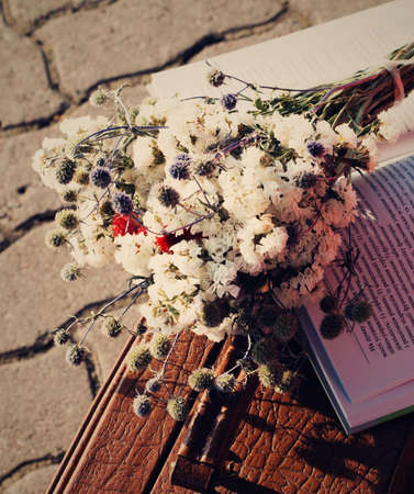 Flowers and a book on an old suitcase, vintage photo.