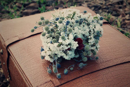 Beautiful wildflowers on an old brown vintage suitcase. Photo in retro style Archivio Fotografico