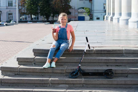 Teenage girl with lemonade in a plastic glass with a straw and with a scooter on a step in the city.