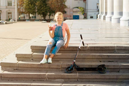 Teenage girl with lemonade in a plastic glass with a straw and with a scooter on a step in the city