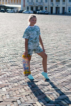 Teenage girl with a skateboard in the city center on a warm summer evening.