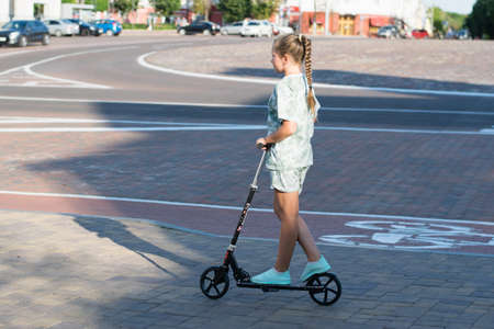 Beautiful teen girl rides around town on a scooter sunny summer evening