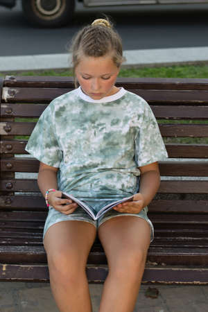 Teen girl sitting in the park and reading a book on a warm summer evening. Leisure of teenagers without a telephone Archivio Fotografico