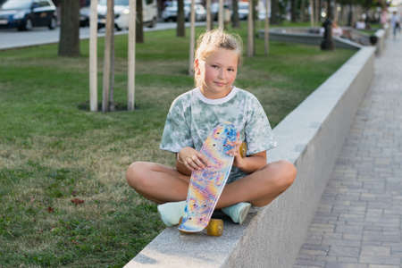 Teen girl sitting in the park with a skateboard in his hand. Leisure of teenagers without gadgets.