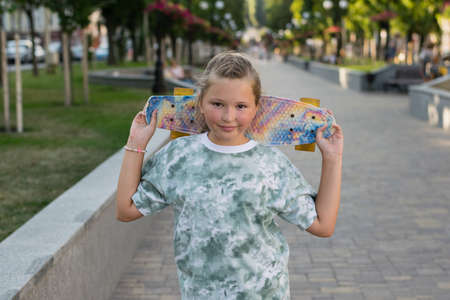 Beautiful girl with a skateboard in the park on a warm summer evening Archivio Fotografico