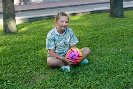 Beautiful girl on the grass in the park with a ball on a warm summer day. Archivio Fotografico