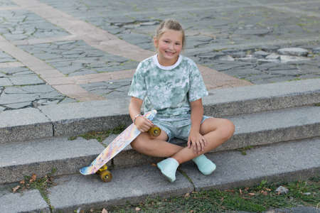 Happy cute teenage girl sitting with skateboard on the steps in the city on a summer day.