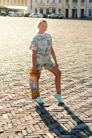 Smiling teenager girl with a skateboard in the city at sunset on a warm evening.