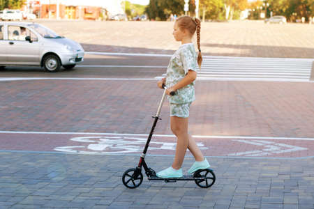 Cute teen girl rides around town on a scooter sunny summer day