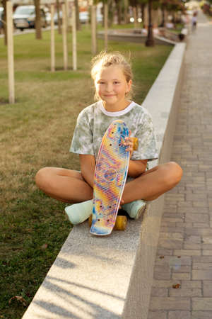 Cute smiling teenage girl with a skateboard in the park on a summer sunny day