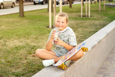 Cute smiling teenage girl with a skateboard in the park on a summer sunny day drinks juice or lemonade