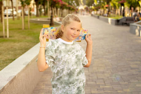 Cute smiling teenager girl with skateboard in the park on a summer sunny day having fun. Healthy lifestyle and leisure concept for teenagers. Archivio Fotografico
