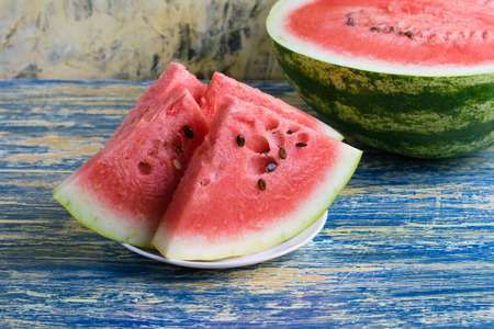Appetizing slices of ripe watermelon on a white plate and half a watermelon on the background. The concept of summer recreation and proper nutrition