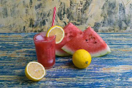 Summer drink watermelon and lemon smoothie in a glass glass with ice and a straw, sliced fruits. The concept of tasty and proper nutrition Archivio Fotografico