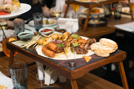 Grilled meat, vegetables and bread with sauce and chips on a wooden tray in the banquet hall during a corporate event.