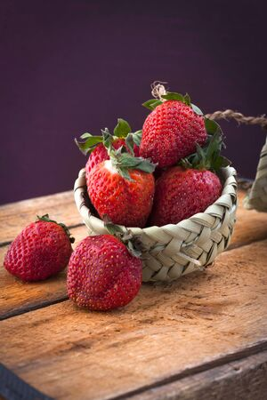 Strawberry in basket with wooden table Stock Photo