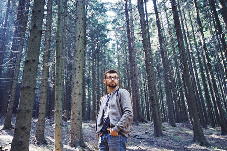 oneness: Young beautiful brunette man with glasses standing in the pine forest. Portrait of a stylish man.