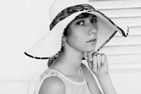 arrogance: Beautiful young girl with beauty skin and a thoughtful look in the big white hat