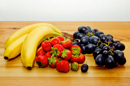 garden stuff: Still life of natural fresh fruit. Bananas, strawberries and blue grapes on the table.