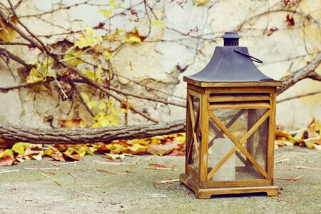 autumn garden: Old wooden lamp with a candle in autumn garden Stock Photo