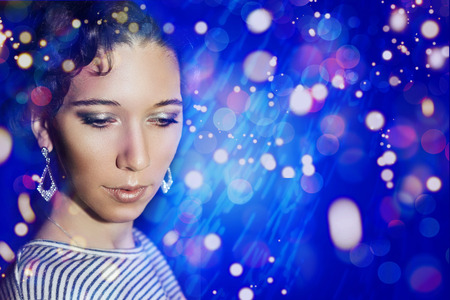 maquillage: Young beautiful girl with a New Years make-up on New Years party. Portrait of a girl in blue lights. New Years Eve 2016.