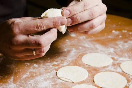 preparing dough: Mans hands preparing dough for ravioli, tortellini. Making baking.