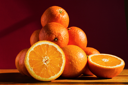 Still life with oranges on a wooden table. Pyramid of orange fruit on a dark background.