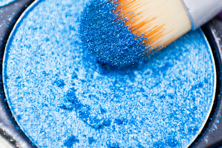 crumbly: Brushes for make-up on the eye shadow palettes. Texture of crumbly  blue sparkling shadows. Stock Photo