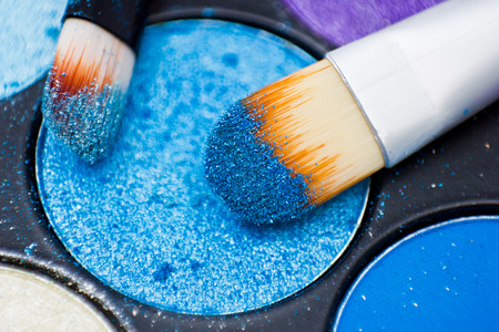 macro close up: Brushes for make-up on the eye shadow palettes. Texture of crumbly  blue sparkling shadows. Stock Photo