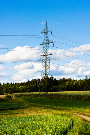 electrical tower: Electrical tower with power lines in a field under a blue sky. Environment and energy. Stock Photo