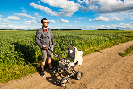 young leave: Young father walking with a baby stroller on nature. Parenting and fatherhood on maternity leave. Stock Photo