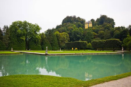 Big pond with azure water in the park of the palace Hellbrunn in Salzburg, Austria. Artificial reservoir in the territory of the estate