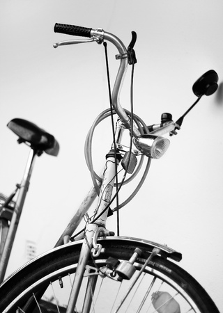 Old retro cruiser bike. Front view. Steering wheel, tire, breaks, seat, mirror and safety lock visible. Black and white. photo
