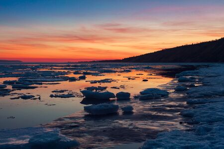 Ice floes floating on the water in the lake. Sunset