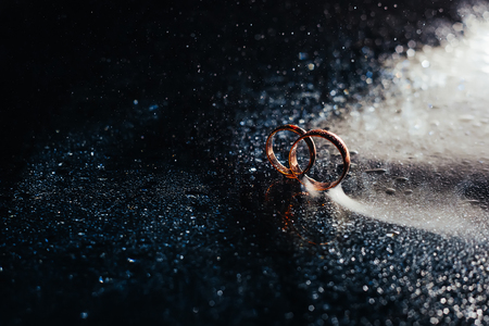 Wedding rings on dark surface shining with light close up macro. Water splashes. Reflection. Lights and smoke. Pair Ring
