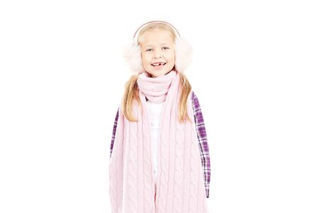 Portrait of little girl wearing scarf and winter ear muffs on white background