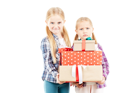 Little sisters posing with Christmas gifts on white background Stock Photo