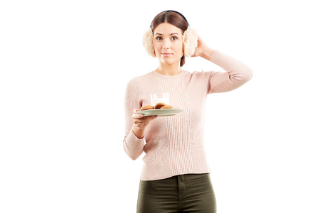 Studio portarit of young woman in earmuffs holding plate with biscuits Stock Photo