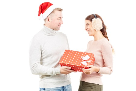 Studio portrait of man and woman with Christmas present on white background