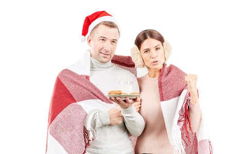 Portrait of couple wrapped in blanket, man wearing Santa hat